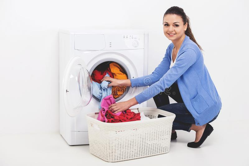 Young woman loading clothes in washing machine. stock photo