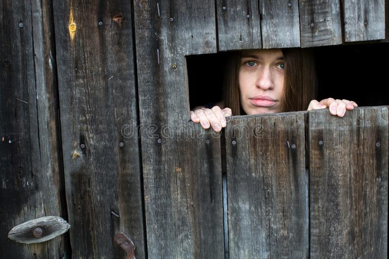 Young woman locked in a wooden shed. royalty free stock photography