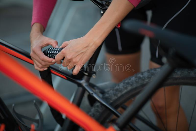 Young woman locking her mountain bike with a numeric lock stock photos