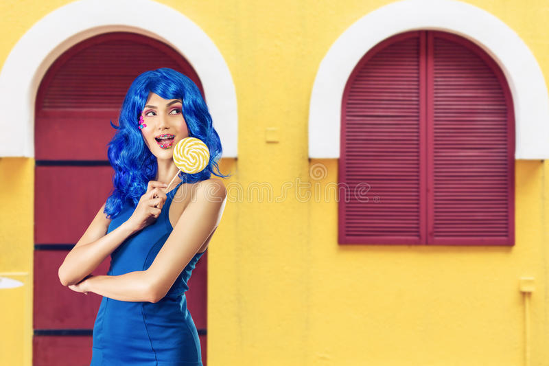 Young woman with lolipop. Fashion young woman with sweet makeup holding lollipop in her hands royalty free stock photography