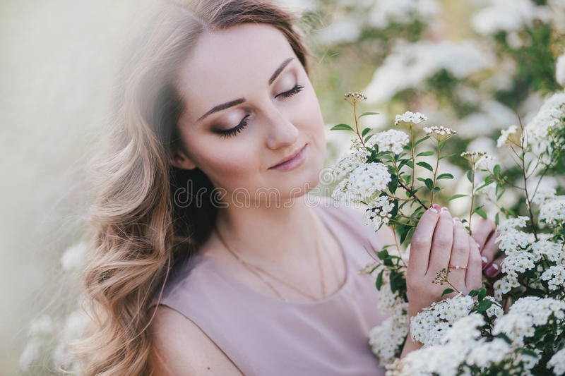 Young woman with long beautiful hair in a chiffon dress posing with lilacin garden with white flowers stock images