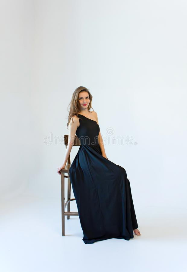 Young woman in long black dress, sitting on the chair isolated on white background royalty free stock photo