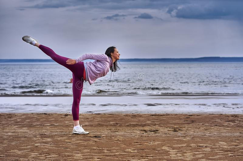 A young woman with long black hair is engaged in gymnastics on the sandy shore of a large river. stock photo