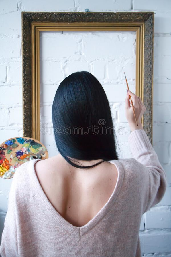 A young woman with long black hair is holding her back holding a brush and a palette with colorful paints on a background of an royalty free stock photo