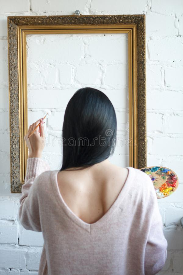 A young woman with long black hair is holding her back holding a brush and a palette with colorful paints on a background of an stock photography