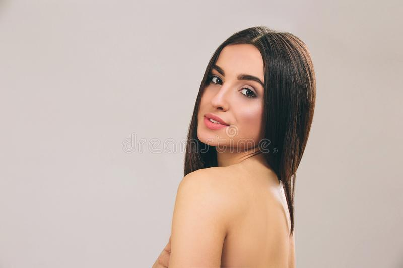 Young woman with long black hair posing on camera. Looking straight and smile. Smooth hair. Beautiful model. Isolated on stock photography
