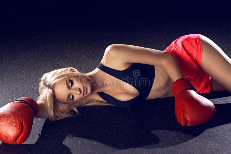 Attractive blonde woman in red boxing gloves lying on floor. Young woman with long blonde hair and closed eyes, dressed in fitness clothing and wearing red royalty free stock images
