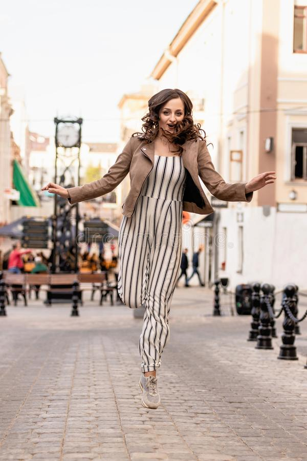 Young woman with long brown hair happily bounces on the background of the street stock photography