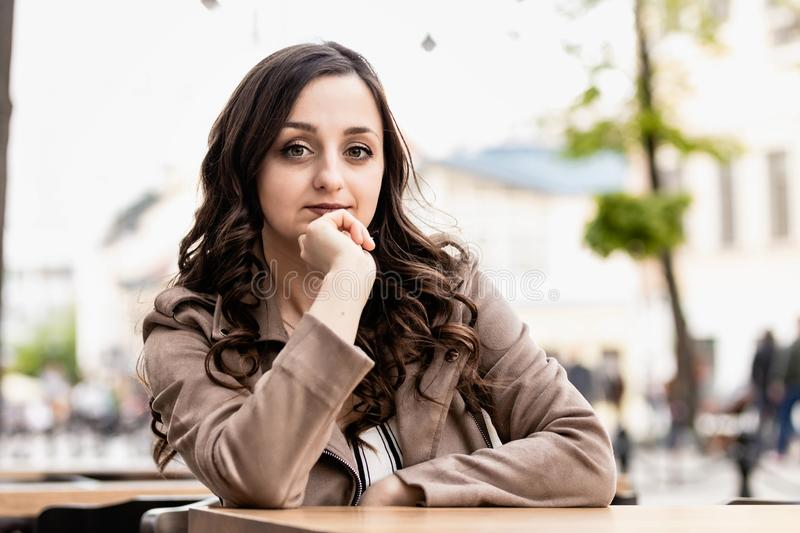 Young woman with long brown hair young beautiful white woman with curly brown hair at a table against the background of the street stock images