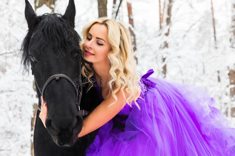Young woman in long dress riding a horse in winter stock photo