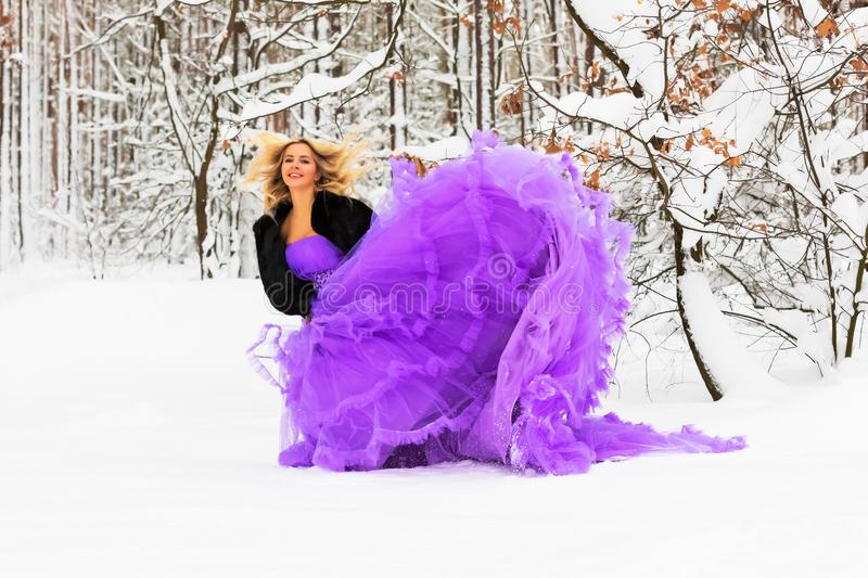 Young woman in a long dress in winter forest. Young beautiful blond woman in a long purple dress in the snowy winter forest or wood outdoors royalty free stock images