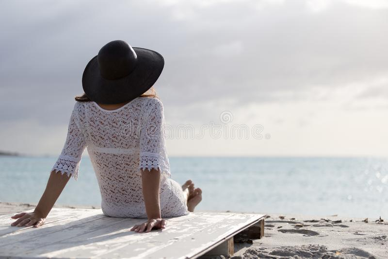 Young woman with long hair from behind sitting by the sea looks at the horizon at dawn in the wind, dressed in a white lace dress stock photos