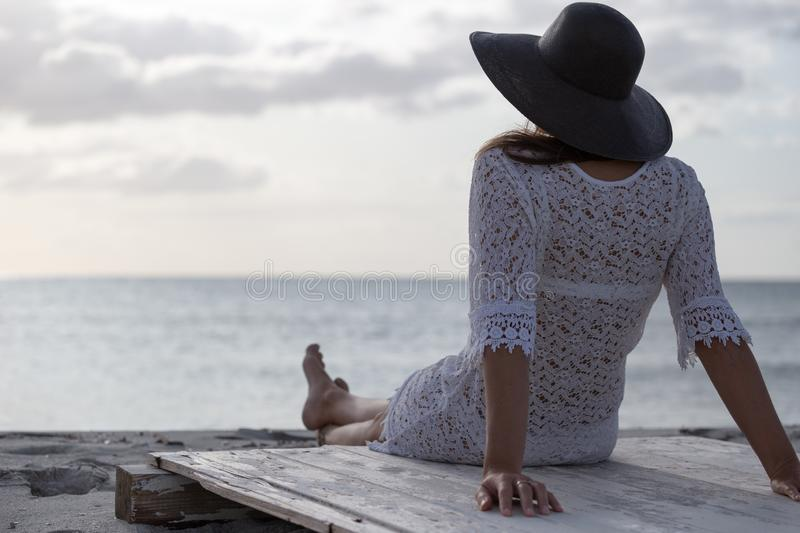 Young woman with long hair from behind sitting by the sea looks at the horizon at dawn in the wind, dressed in a white lace dress. White underwear and large stock image