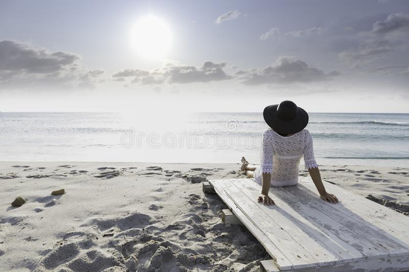 Young woman with long hair from behind sitting by the sea looks at the horizon at dawn in the wind, dressed in a white lace dress. White underwear and large stock images