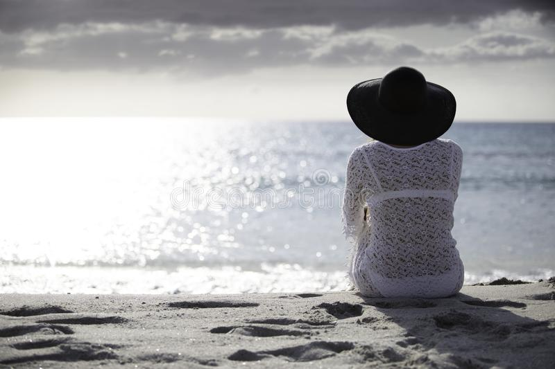 Young woman with long hair from behind sitting by the sea looks at the horizon at dawn in the wind, dressed in a white lace dress. White underwear and large royalty free stock images