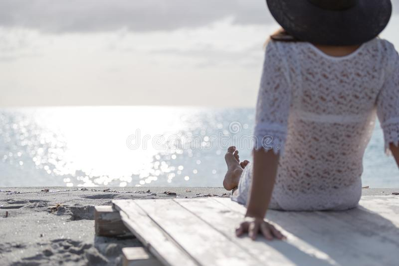 Young woman with long hair from behind sitting by the sea looks at the horizon at dawn in the wind, dressed in a white lace dress stock images