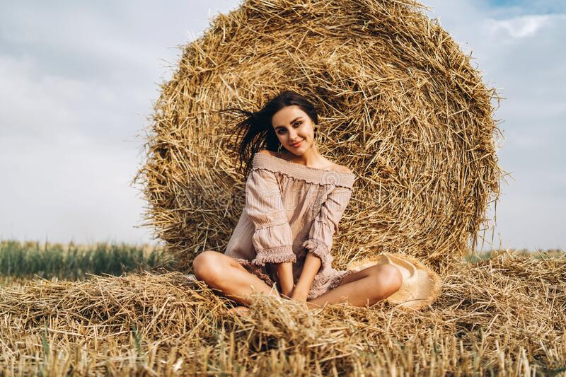 A young woman with long hair and in a dress sits near a hay bale. Woman posing smiling and looking at camera.  stock photography