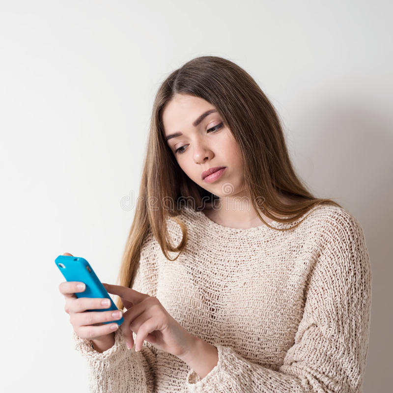 Young woman with long hair looking into the phone. Haired young woman talking on a smartphone royalty free stock image