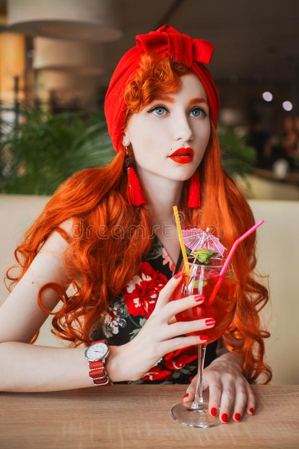 Young woman with long hair, pale skin and in rose summer dress. Beautiful redhead model drink fruit summer cocktail in cafe. Fashi royalty free stock photography