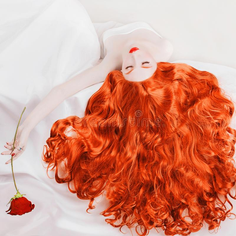 Young woman with long hair, pale skin on white background. Beautiful redhead model lying in bed. Fashion style. Girl with long red curly hair holds a rose in stock photos