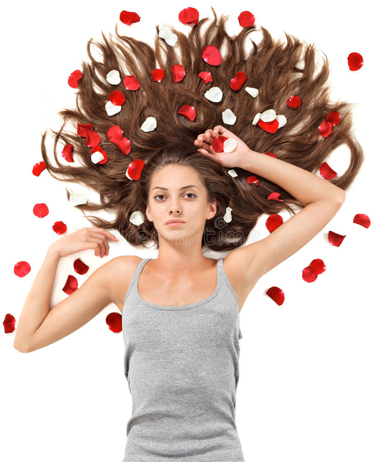 Young woman with long hair and rose petals. Young beautiful brunette woman with scattered long hair and rose petals on white stock photo