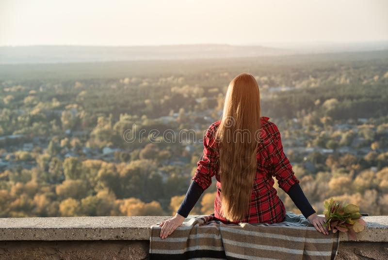 Young woman with long hair sits on a hill overlooking the village. Back view stock photos