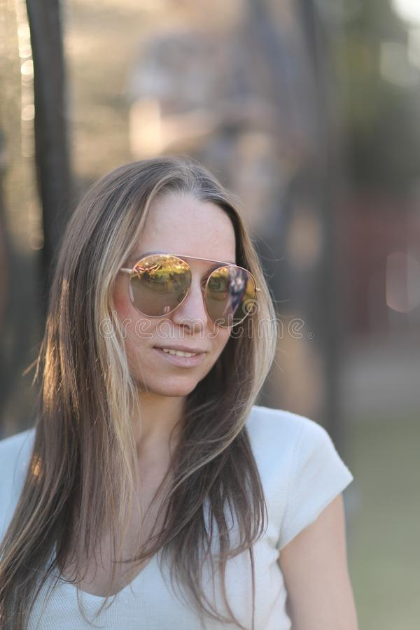 Young woman with long hair in sunglasses stock photography