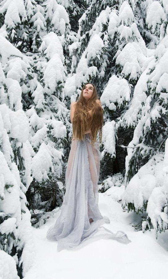 Young woman with long hair, with long white dress in snow. Ice freezes in winter, looks up and warms with her arms royalty free stock images