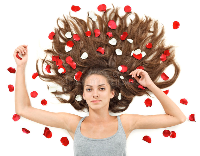 Young woman with long hairs and rose petals stock image