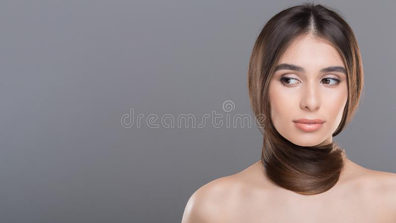 Young woman with long healthy hair around neck as scarf. Natural haircare. Young woman with long healthy hair around neck as scarf, panorama with empty space royalty free stock photo