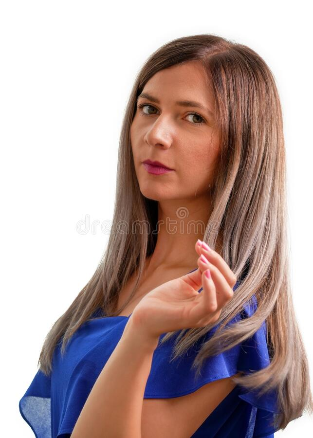 Young woman with long light brown hair and blue dress, looking in camera, studio shot on white background.  royalty free stock image