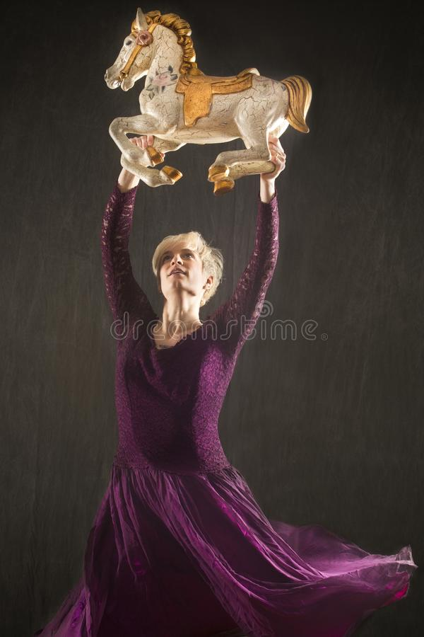Young woman in purple dress dancing with antique carousel horse. stock photo