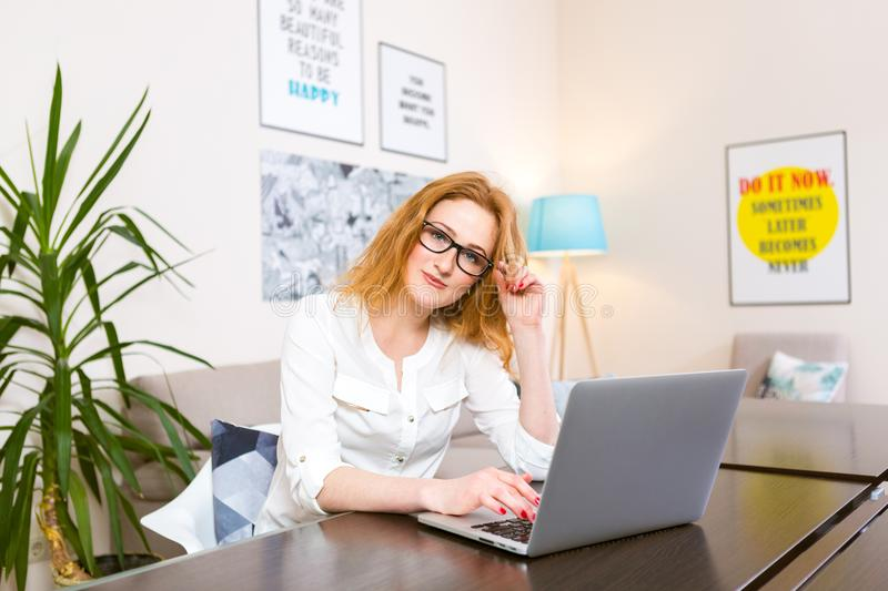 Young woman with long red hair and glasses for view works, prints on a gray laptop keyboard sitting at a wooden table in a bright. Interior. Subject business stock photography