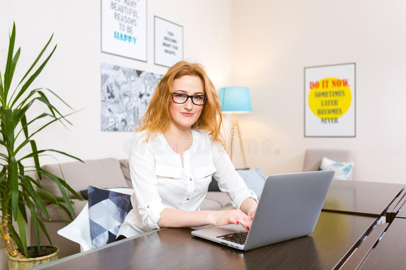 Young woman with long red hair and glasses for view works, prints on a gray laptop keyboard sitting at a wooden table in a bright. Interior. Subject business royalty free stock photography