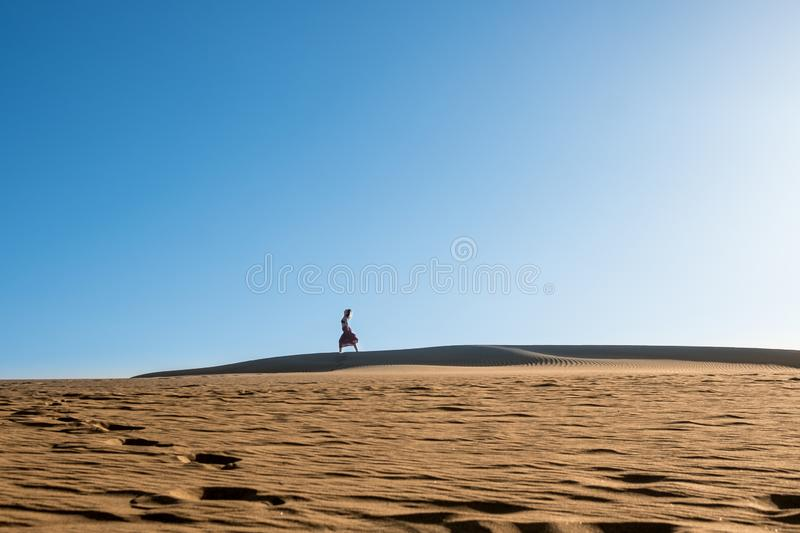 Young woman with long skirt dancing in the distance in evocative and confident way on top of desert dune with clear blue sky royalty free stock photography