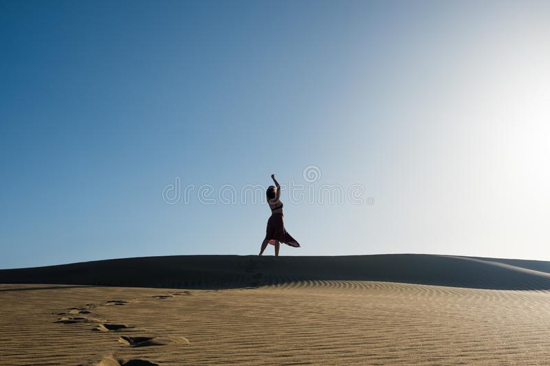 Young woman with long skirt dancing in the distance in evocative and confident way on top of desert dune with clear blue sky royalty free stock photos