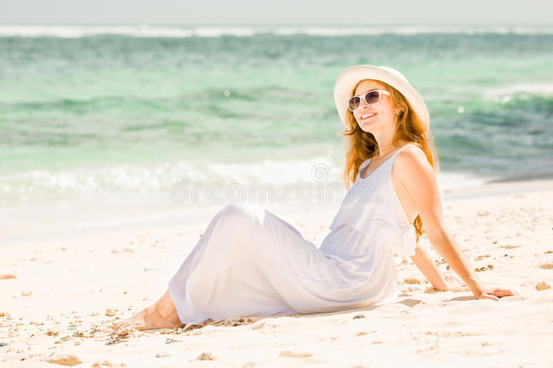 Young woman in long white dress and hat relaxing stock image