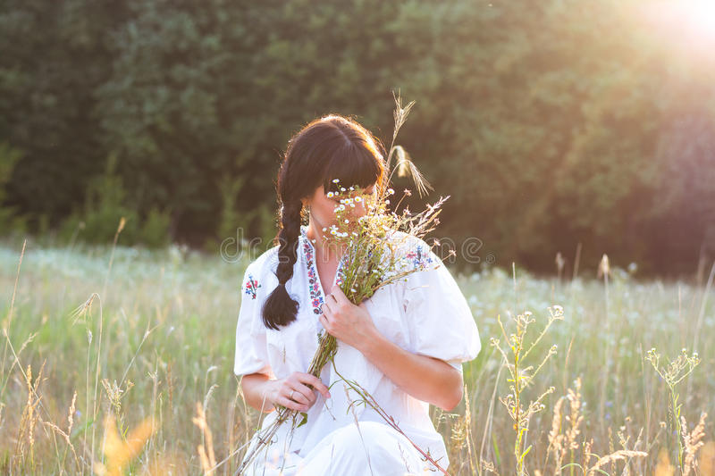 A young woman in a long white embroidered shirt сovered her face with flowers in a meadow at sunset. royalty free stock image