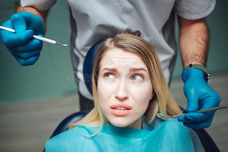 Young woman look at tools for teeth treatment with fear. She sit in chair in dentistry. Dentist stand behind her. stock photos