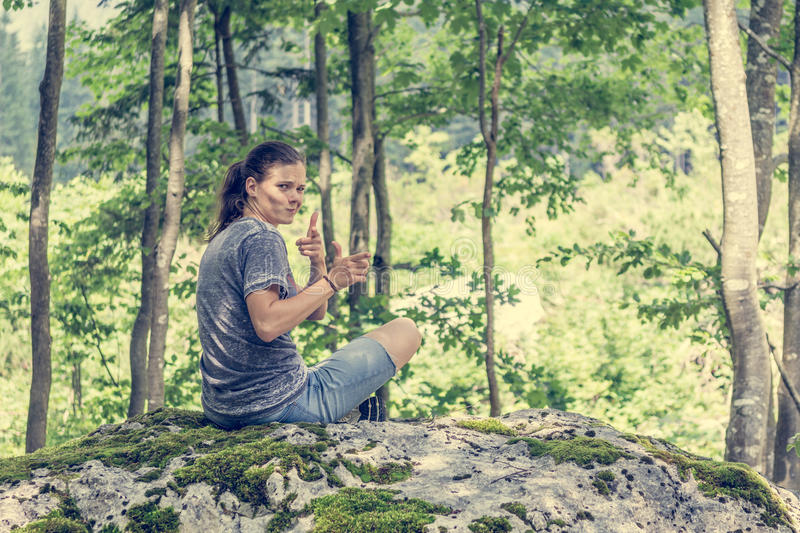 Young woman looking across her shoulder on a forest rock. stock images