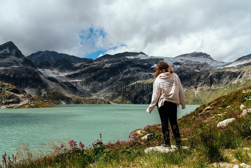 Young woman looking at mountain lake in the Alps royalty free stock photography