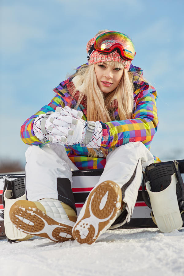 Young woman looking away while holding snowboard in snow. Happy young woman looking away while holding snowboard in snow stock images