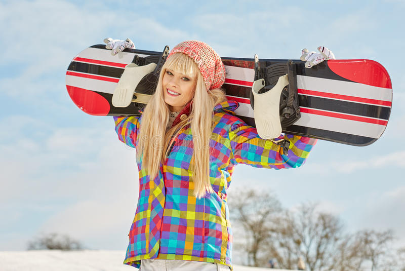 Young woman looking away while holding snowboard in snow. Happy young woman looking away while holding snowboard in snow stock photography