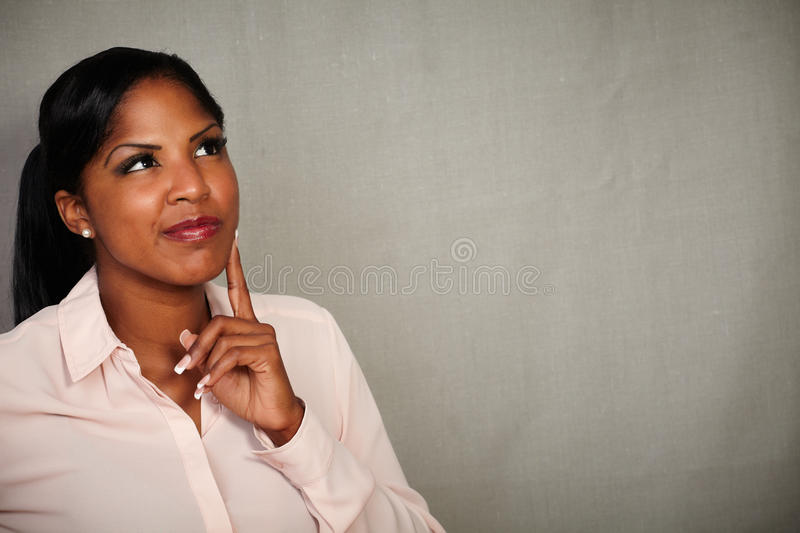 Young woman looking away with a thinking gesture stock photos