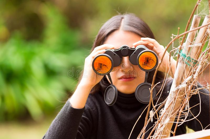 Young woman looking through black binoculars in the forest in a blurred background royalty free stock photo