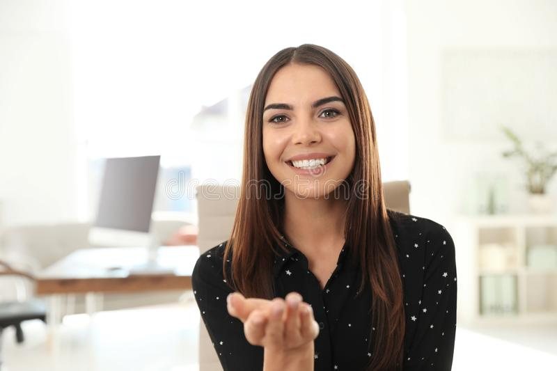 Young woman looking at camera and using video chat in home office royalty free stock photography
