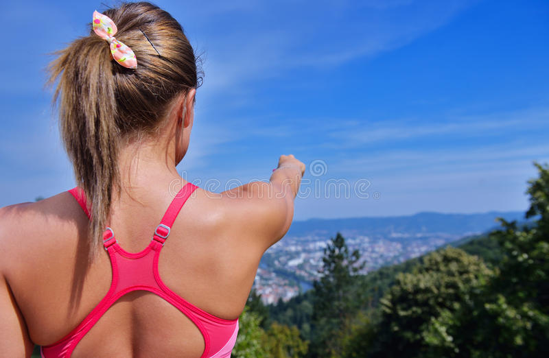 Young woman looking at city in background, beautiful inspirational landscape. Young woman looking at city in background, inspirational landscape hiking trekking royalty free stock photography