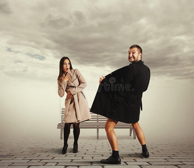Young woman looking at crazy man in coat. Startled young women looking at crazy men in coat on the street royalty free stock photo