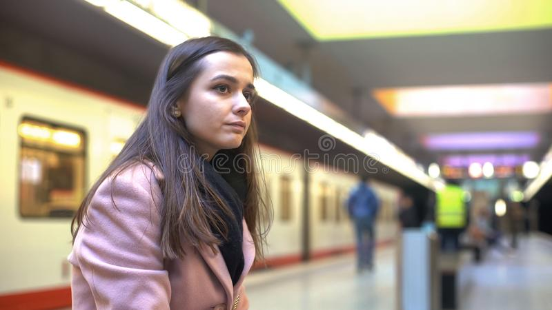 Young woman looking at departing train, late for work, lost opportunity concept. Stock photo stock photos