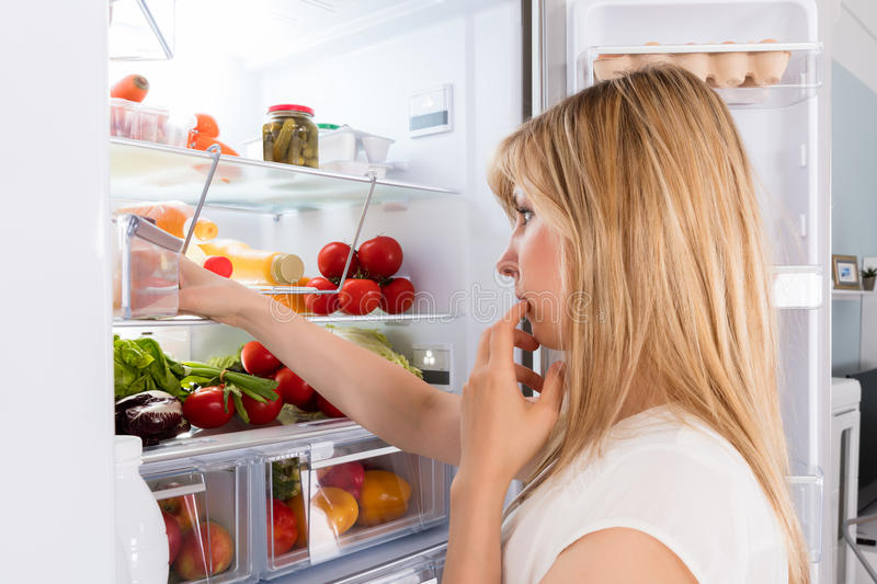 Young Woman Looking In Fridge stock photo